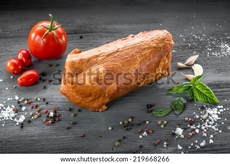 Smoked meat on wooden grey desk with spices - stock photo