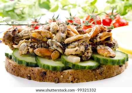 smoked oysters on half a bun with tomato and cucumber - stock photo