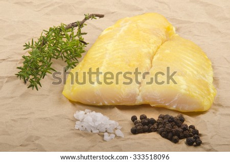 smoked river cobbler with thyme, pepper and coarse salt on brown kitchen paper - stock photo