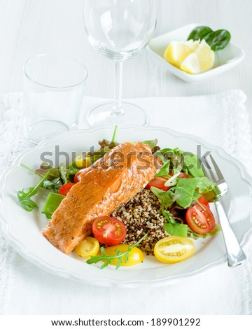 Smoked salmon and colorful quinoa salad with cherry tomatoes and snow peas - stock photo