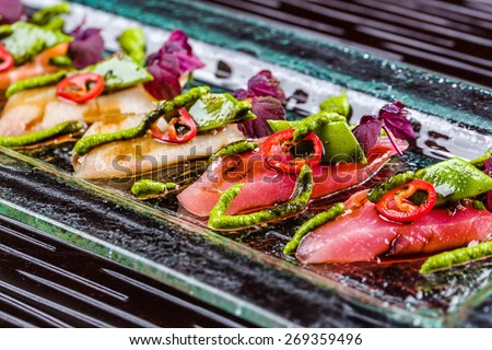 Smoked salmon and tuna decorated with avocado, pepper and wasabi and served on the glass plate - stock photo