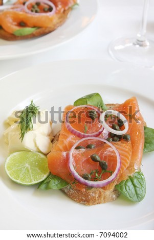 Smoked salmon appetizer, on toasted rye bread, with baby spinach leaves, red onion, capers, and dill, served with creme fraiche and lime.  Delicious! - stock photo