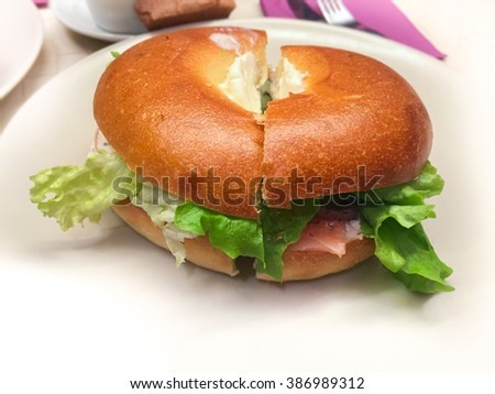 Smoked salmon bagel cut in half on white plate - stuffed with salad and sour cream