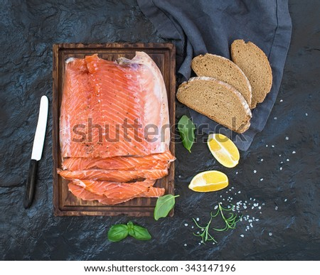 Smoked salmon fillet with lemon, fresh herbs and bred on wooden serving board over dark stone backdrop, top view - stock photo