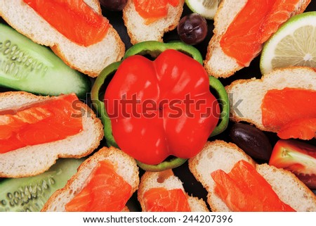 smoked salmon on baguette with olives and pepper - stock photo
