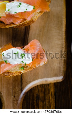 smoked salmon on toasted bread with cream fresh, lemon and chives on wooden background - stock photo