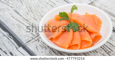 Smoked salmon pieces in white bowl over wooden background