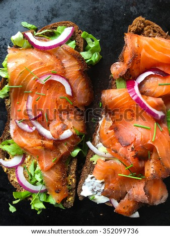 Smoked salmon sandwich with lettuce, onion and chives - stock photo