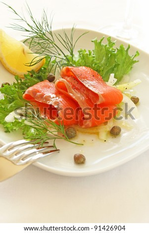 Smoked salmon served with lemon and salad - stock photo