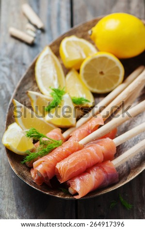 Smoked salmon with grissini and lemon, selective focus - stock photo