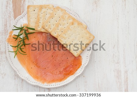 smoked salmon with toasts on white plate
