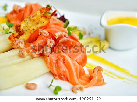 Smoked salmon with white asparagus, gray shrimps and spices on white plate - stock photo