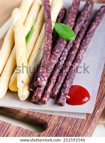 Smoked thin sausages and breadsticks on board