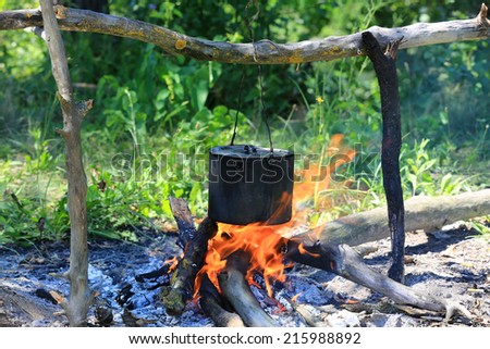 Smoked tourist kettle on camp fire  - stock photo