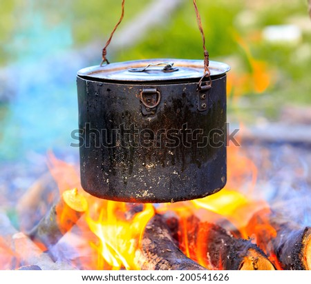 Smoked tourist kettle on campfire  - stock photo