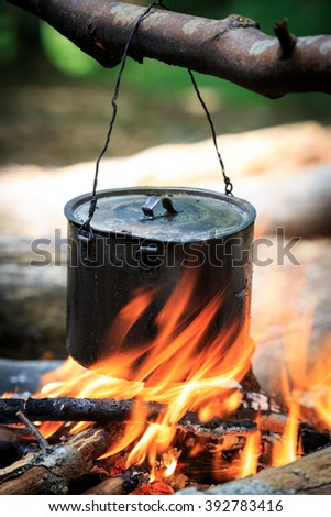 smoked tourist kettle over fire in camp - stock photo