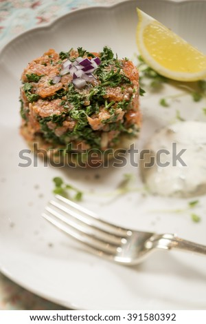 Smoked Trout and Quinoa Cake with a Lemon and Dill Sauce, with a Lemon Wedge on a White Plate - stock photo