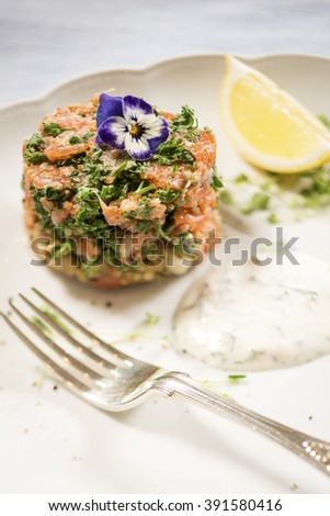 Smoked Trout and Quinoa starter with a Lemon and Dill Sauce, with a Lemon Wedge on a White Plate - stock photo