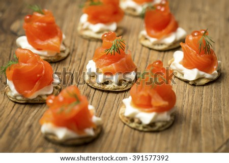 Smoked Trout Canapes with dill and horseradish cream on a textured wooden background - stock photo