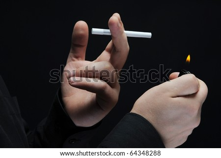 smokes a cigarette on a dark background - stock photo