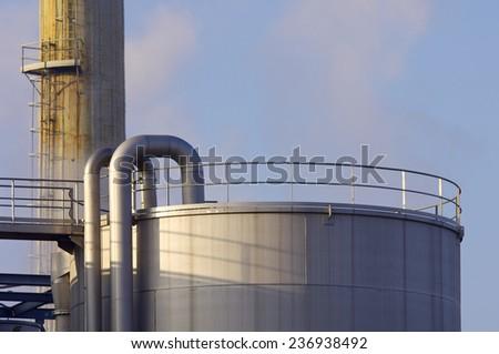 Smokestack and tank of a factory in Zaragoza, Aragon, Spain - stock photo