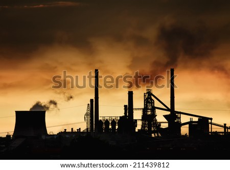 Smokestack in factory with yellow sky and clouds. Industrial pollution. - stock photo