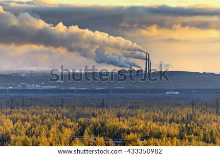 Smokestack that pollute the atmosphere. Ecological catastrophy. Polar tundra, deep autumn. Sunset, bad lighting conditions. - stock photo