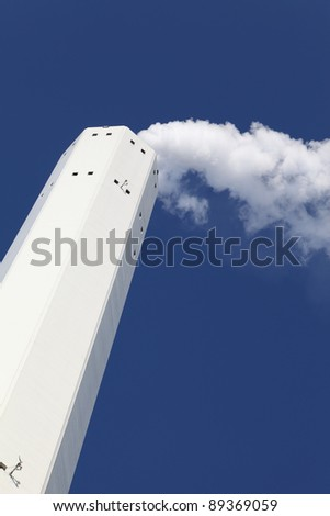 Smokestack with pollution against a blue sky - stock photo