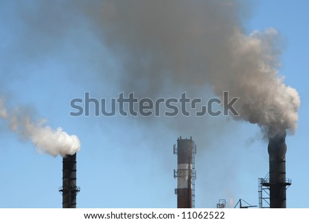 Smokestacks belching pollution against a blue sky