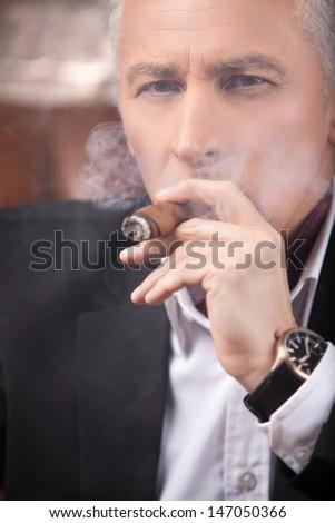 Smoking a cigar. Successful mature businessman smoking a cigar and looking at camera - stock photo