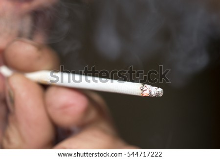 smoking a cigarette in his hand on black