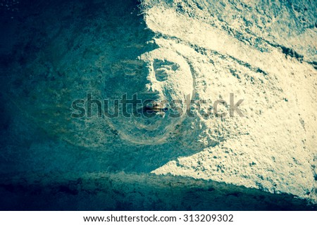 Smoking addiction. Stone human face (old building architectural detail) with real cigarette in the mouth. Toned photo. - stock photo