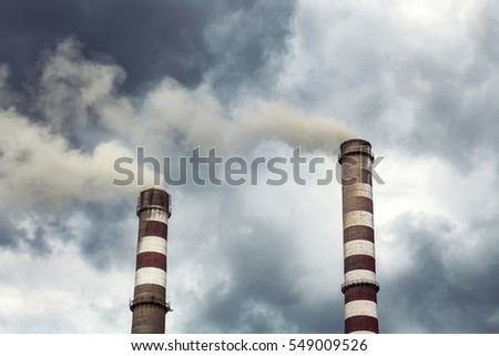 Smoking big industrial chimneys in dark clouds. Concept for environmental protection.
