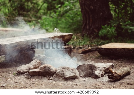 Smoking campfire on the nature. Camping place with wooden benches in summer forest. Campsite with campfire. Place for camping. Camp site in the forest on nature outdoors. - stock photo