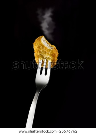 Smoking Chicken nugget on fork against black background