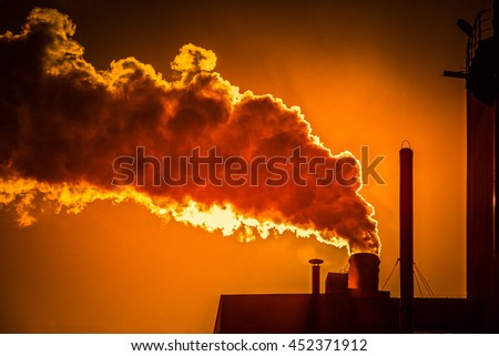 smoking chimney of a factory at sunset