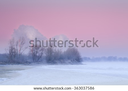 Smoking chimneys over a misty and freezing river during dusk