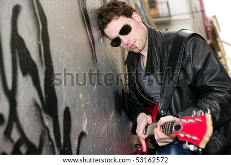 smoking cigarette rock leather boy playing guitar outdoor on silver wall background - stock photo