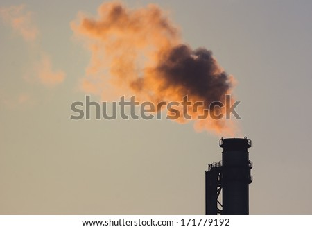 smoking factory chimney in the morning light - stock photo