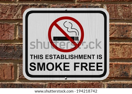 Smoking Free Establishment Sign, An red and white sign with cigarette icon and not symbol with text on a brick wall - stock photo