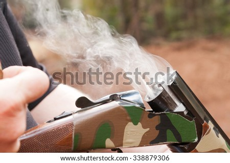 Smoking gun concept,  a double barrelled over/under shotgun immediately after firing with shallow depth of field focused on the smoke leaving the breech