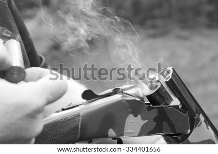 Smoking gun concept,  black & white of a double barreled over/under shotgun immediately after firing with shallow depth of field focused on the smoke leaving the breech - stock photo