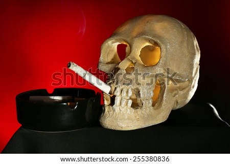 Smoking human scull with cigarette in his mouth on dark color background - stock photo