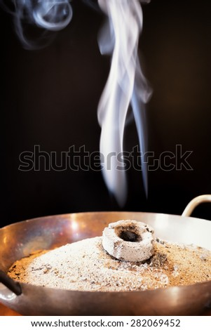 smoking incense in a pot with coal