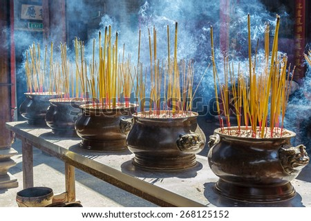 Smoking incense sticks at the Thien Hau Temple in Ho Chi Minh City. The incense is lit as an offering to the gods. - stock photo