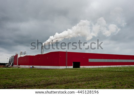 Smoking industrial pipes. red shed with a chimney and smoke - stock photo