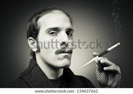 Smoking jacket wearing man smoking a cigarette through cigarette holder - stock photo