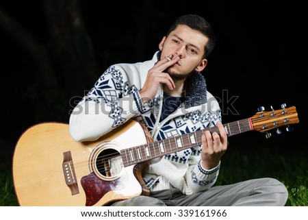 Smoking man in a white north sweater on a grass with a guitar