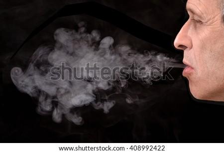 Smoking man portrait on black background.Blowing smoke. - stock photo