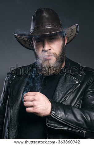 Smoking man with a beard and mustache wearing a cowboy hat